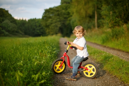 Little toddler boy learning to ride on his first bike  in summer forest Stock Photo