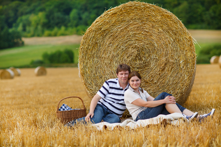 Young couple picknicking on yellow hay field on summer evening Stock Photo - 22427818