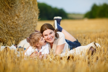 Young mother and her little son having fun at picnicking on yellow hay field in summer photo