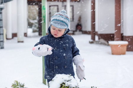 Cute baby boy in winter clothes playing with snow photo