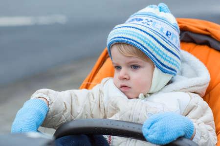 baby stroller: Little  boy one year old in warm winter clothes and orange pram outdoor