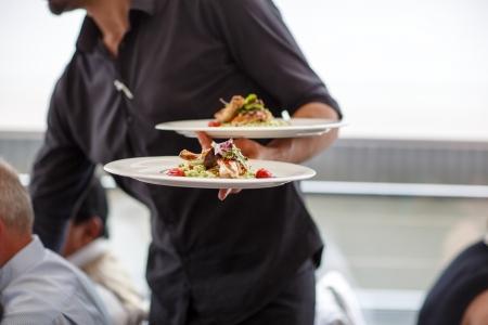Kelner niosąc talerz z naczynia sałatka na weselu