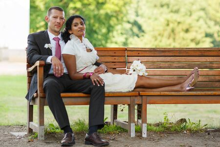 Beautiful indian bride and caucasian groom, in summer park photo