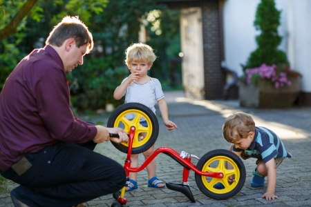 Portrait of two cute boys repairing bicycle wheel with father outdoors photo