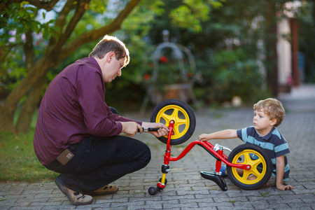 Little boy and his father repairing bicycle wheel outdoors photo