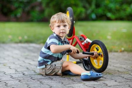 Kleine peuter jongen repareren van zijn eerste fiets