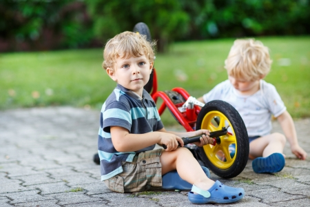 Two little boys, siblings, repairing bicycle outdoors photo