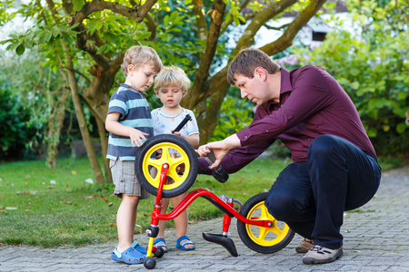 young man and two little sons repairing bicycle outdoors photo