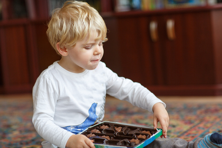 Cute toddler boy of two years eating chocolate praline photo