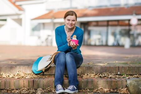 Young woman eating ice cream in summer city photo
