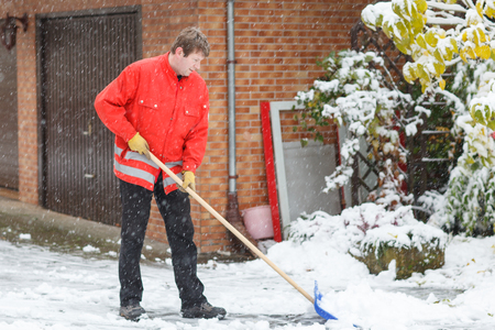 Adult young man clean owns road to home against snow Stock Photo