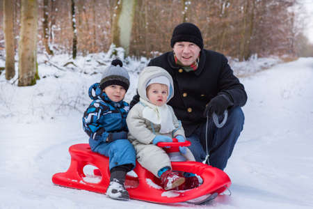 Two little siblings and their father having fun on sledge on winter snow day photo