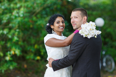 Beautiful indian bride and caucasian groom in summer park photo