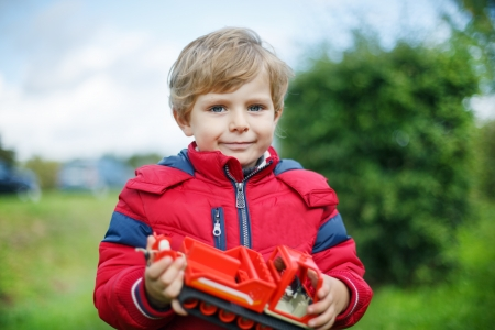 Beautiful toddler boy in red clothes with ship toy in hand