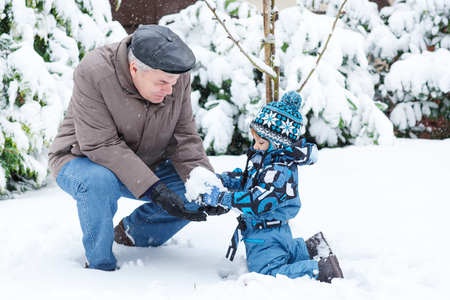 Grandfather and granchild having fun with snow outdoors on beautiful winter day Stock Photo - 23546210
