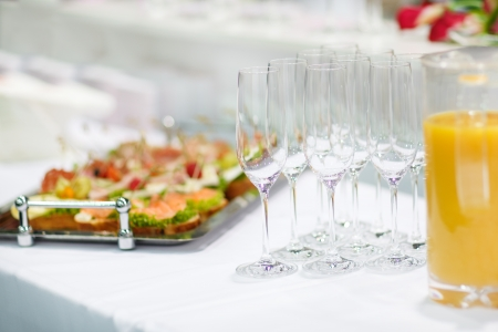 Empty champagne glasses and finger food on festive wedding table photo