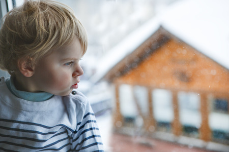 Little toddler boy looking out of the window on winter day with snow landscape photo