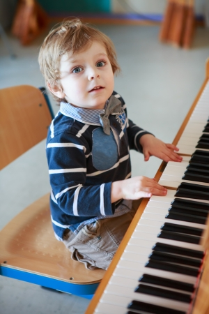 prodigy: Little toddler boy playing piano at music school Stock Photo