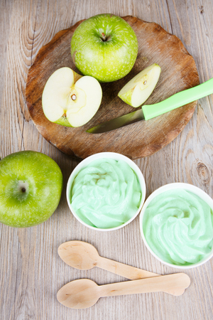 frozen joghurt: Serving of frozen homemade creamy ice yoghurt  with fresh green apples and wooden spoon Stock Photo