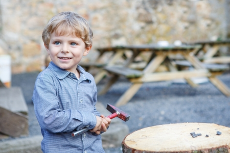 Little blond boy playing with hammer outdoors photo