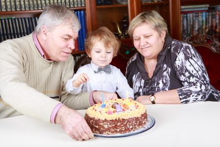 Little boy celebrating his third birthday at home with his grandmother and grandfather Stock Photo - 24132498
