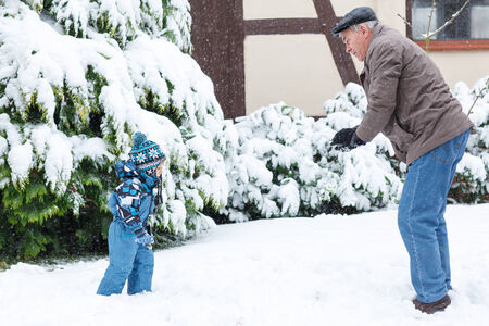 Grandfather and granchild having fun with snow outdoors on beautiful winter day Stock Photo - 24132561