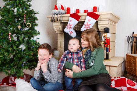 Beautiful young mother and two adorable sibling boys with Christmas tree and decoration. photo
