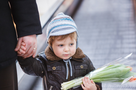 two years: Little toddler boy of two years in a shopping mall with flowers for mother Stock Photo