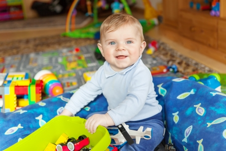 Portrait of adorable baby boy of 6 months playing with toys at home photo