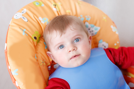 baby on chair: Portrait of cute baby boy of 6 months sitting in baby chair