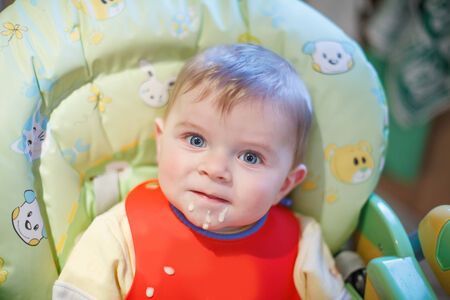 baby on chair: Portrait of cute baby boy of 6 months sitting in baby chair and eating milk mash