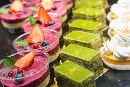 Different kinds of sweet dessert cakes with berries and green tea in a cafe photo