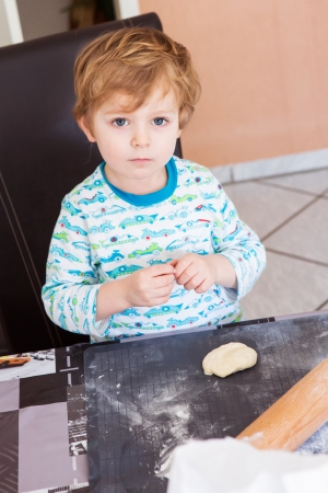 Cute boy of three years helping to bake in home kitchen photo