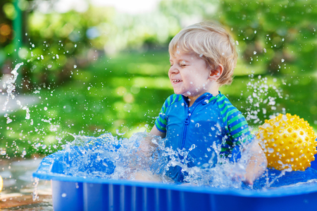 Little toddler boy having fun with splashing water in summer garden pool photo