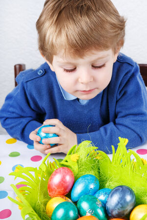 easter egg hunt: Little toddler boy being happy about Easter egg hunt, traditional action in Germany for Eastern holiday