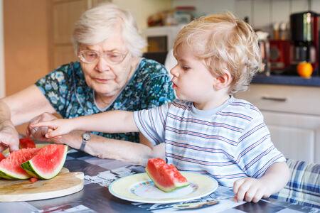 great grandmother: Dos generaciones: Ni�o peque�o y su gran abuela comiendo sand�a en la cocina casera. Enfoque selectivo en el ni�o