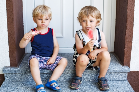 Two little twins boys eating ice cream in summer, outdoors photo