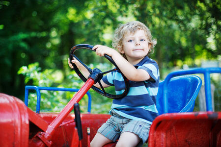 Happy little boy of three years having fun on tractor in summer, outdoors photo
