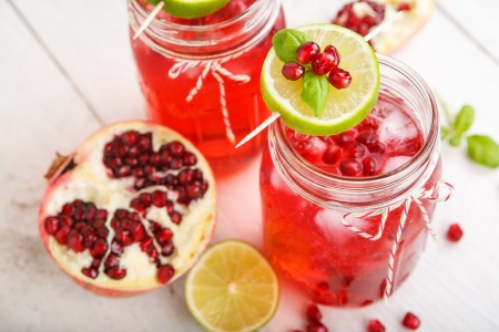 pomegranate juice: Two glasses with red pomgranate juice, lime and mint