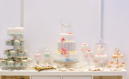 Elegant sweet table with big cake, cupcakes, cake pops on dinner or event party