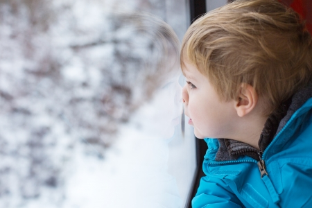 Cute little boy looking out train window outside photo