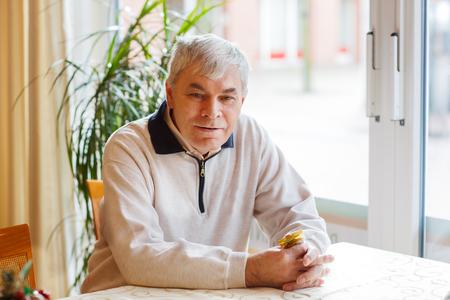 Portrait of senior man near window, indoor Stock Photo - 25431652