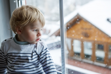 Little toddler boy looking out of the window on winter day with snow landscape Standard-Bild