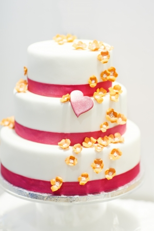 Wedding cake decorated with pink rose flowers and hearts
