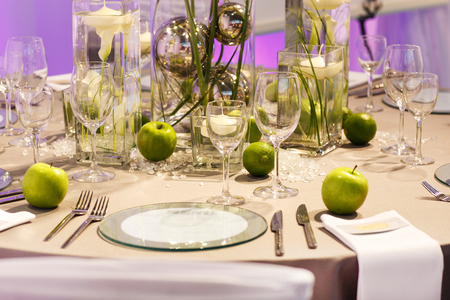 Elegant table set in green, creme and brown with apples and limes for wedding or event party