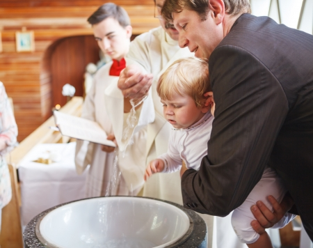 blue church: Little baby boy being baptized in catholic church holding by father