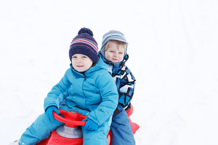 Two little siblings and their mother having fun on sledge on winter day in mountains photo