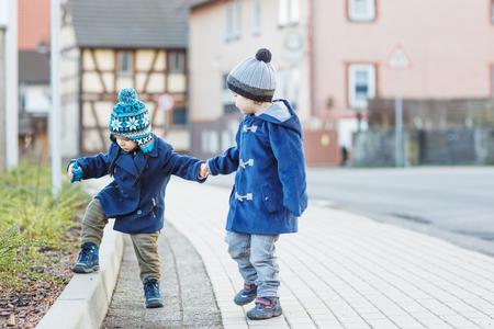 Two little sibling boys walking on the street in German village photo