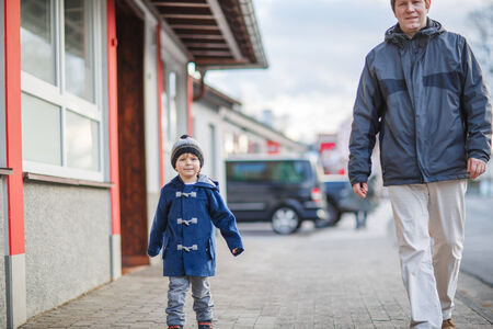 Father and  little son walking on the street in German village photo