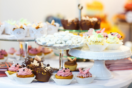 Elegant sweet table with cupcakes, cake pops and candy on dinner or event party photo